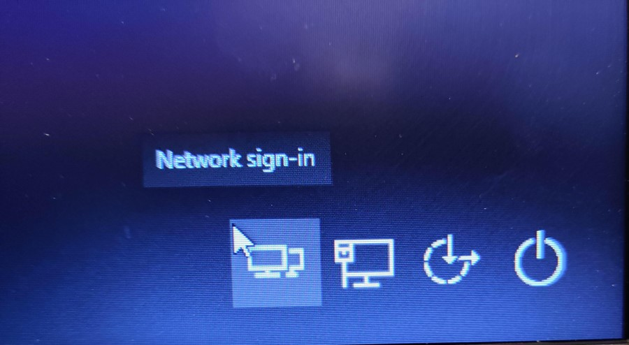Image of logon screen depicting the Network Sign-in button in the lower right hand side of the screen. The network-sign in button looks like two computer monitors, one half obscuring the other.